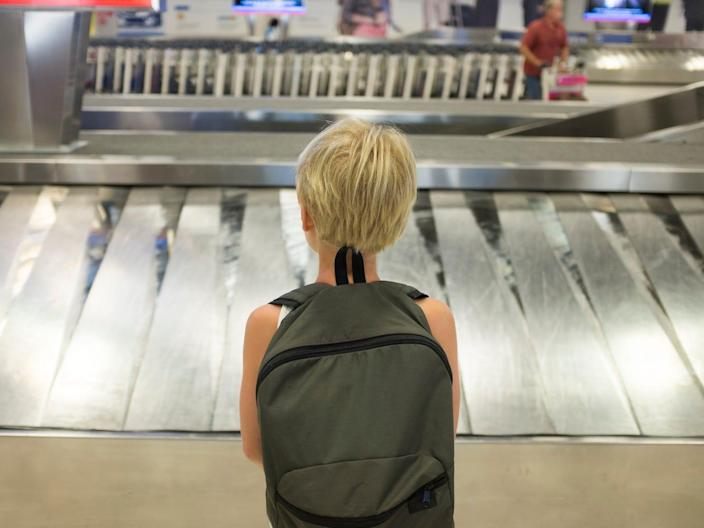 A child stands at the luggage conveyor belt in an airport.