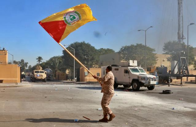A fighter waves a Shiite militia flag in front of U.S soldiers in armored vehicles inside the U.S. Embassy compound in Baghdad on Dec. 31. (Photo: Khalid Mohammed/AP)