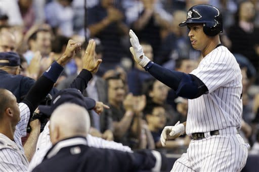 New York Yankees' Alex Rodriguez celebrates with teammates after hitting a third-inning, solo home run during their baseball game against the Kansas City Royals at Yankee Stadium in New York, Wednesday, May 23, 2012. (AP Photo/Kathy Willens)