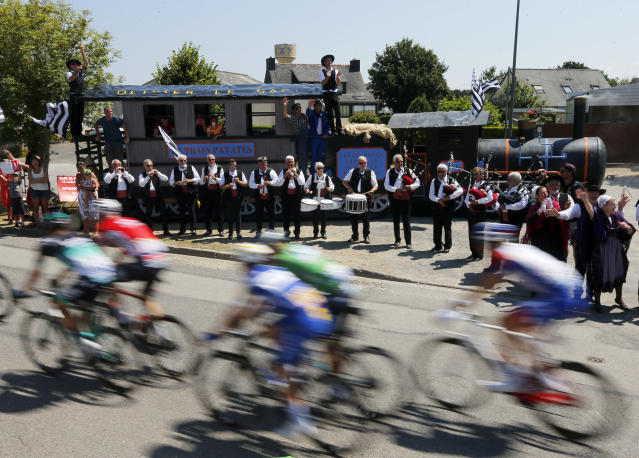 Musicians perform on the side of the road as the pack rides during the sixth stage of the Tour de France cycling race over 181 kilometers (112.5 miles) with start in Brest and finish in Mur-de-Bretagne Guerledan, France, Thursday, July 12, 2018. (AP Photo/Peter Dejong)