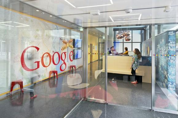 Office entrance with Google logo on glass wall.
