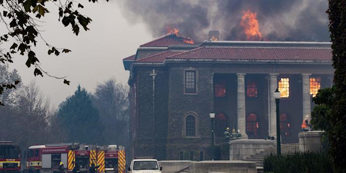 TOPSHOT - Firefighters try, in vain, to extinguish a fire in the Jagger Library, at the University of Cape Town, after a forest fire came down the foothills of Table Mountain, setting university buildings alight in Cape Town, on April 18, 2021. (Photo by RODGER BOSCH / AFP) (Photo by RODGER BOSCH/AFP via Getty Images)