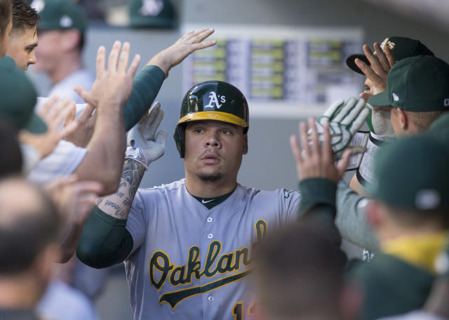 Bruce Maxwell is congratulated by teammates in the dugout after hitting a solo home run off Seattle Mariners starting pitcher Yovani Gallardo on Saturday, Sept. 2, 2017, in Seattle. (AP)