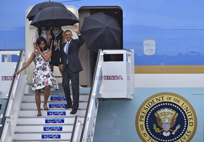 US President Barack Obama waves next to First Lady Michelle Obama as they arrive with their daughters Sasha and Malia (behind) at Jose Marti international airport in Havana on March 20, 2016 (AFP Photo/Yuri Cortez)