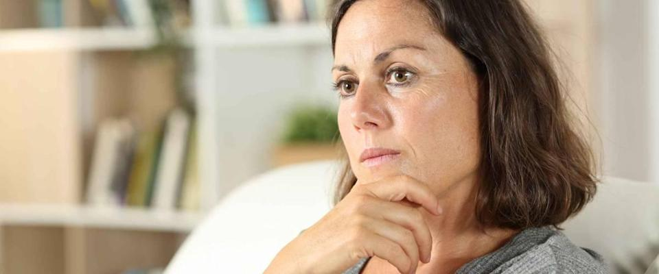 Pensive adult woman looking away sitting in the sofa in the living room at home
