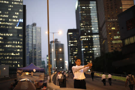 "A man takes a ""selfie"" at a street blocked by pro-democracy protesters outside the government headquarters office in Hong Kong October 9, 2014.  REUTERS/Carlos Barria"