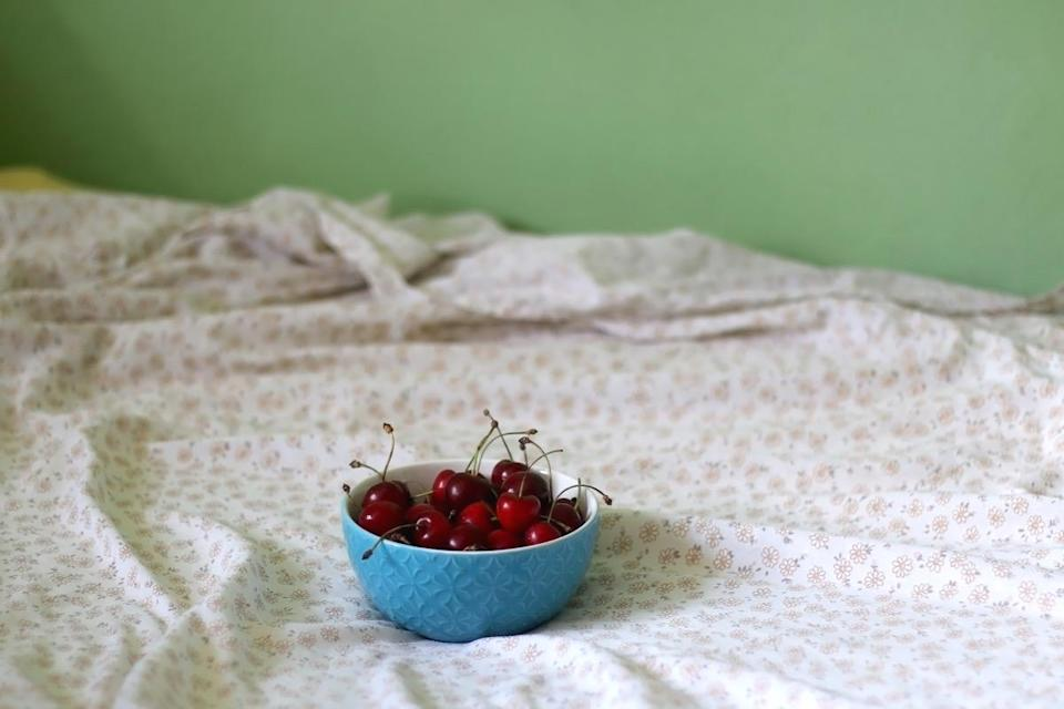 bowl of cherries on bed with floral sheets