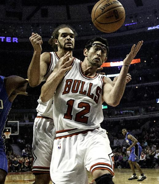 Chicago Bulls' Kirk Hinrich (12) and Joakim Noah try to save the ball from going out of bounds during the first quarter against the Orlando Magic of an NBA basketball game in Chicago on Tuesday, Nov. 6, 2012. (AP Photo/Charles Cherney)