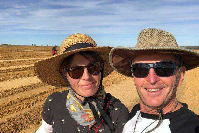 A man and a woman wearing hats and sunglasses smile in a selfie as they stand in a field of dirt.
