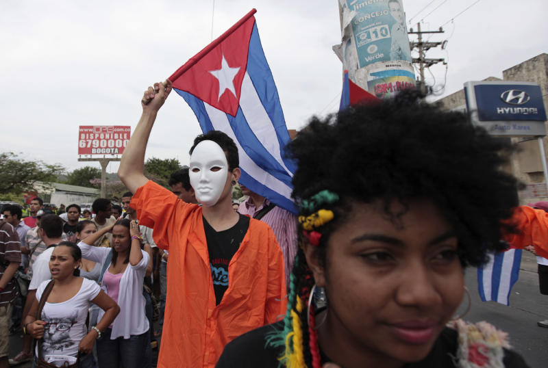 A protester dressed as a detainee from the U.S. military prison at Guantanamo waves a Cuban flag during a march against the sixth Summit of the Americas in Cartagena, Colombia, Saturday April 14, 2012. The summit brings together presidents and prime ministers from Canada, the Caribbean, Latin America and the U.S. (AP Photo/Fernando Llano)