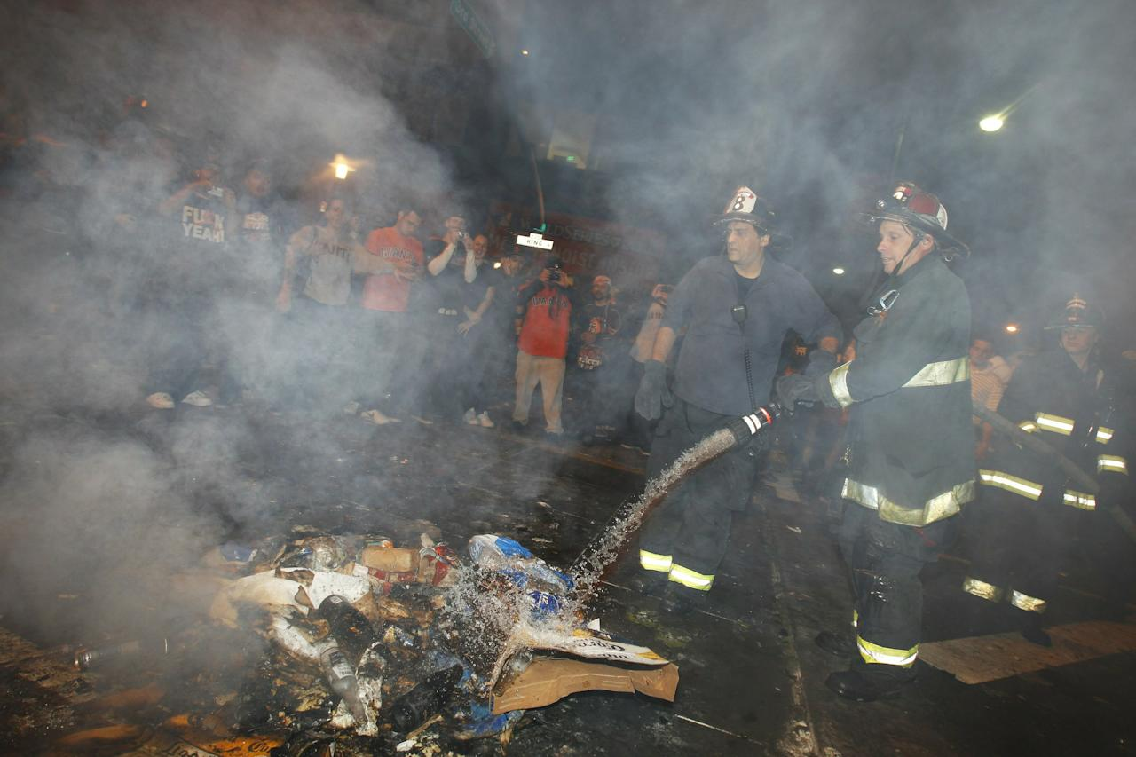SAN FRANCISCO - NOVEMBER 1:  Two firefighters distinguish a small fire as baseball fans celebrate the Giants World Series win on November 1, 2010 in San Francisco, California. The Giants defeated the Texas Rangers 3-1 in game 5 to win their first title in 53 years.  (Photo by Stephen Lam/Getty Images)