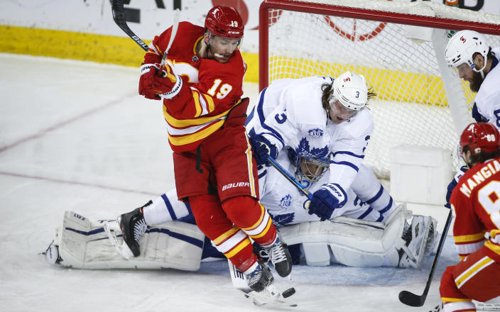 Toronto Maple Leafs' Justin Holl, right, crashes over goalie Frederik Andersen, center, trying keep Calgary Flames' Matthew Tkachuk from the puck during the second period of an NHL hockey game, Tuesday, Jan. 26, 2021 in Calgary, Alberta. (Jeff McIntosh/The Canadian Press via AP)