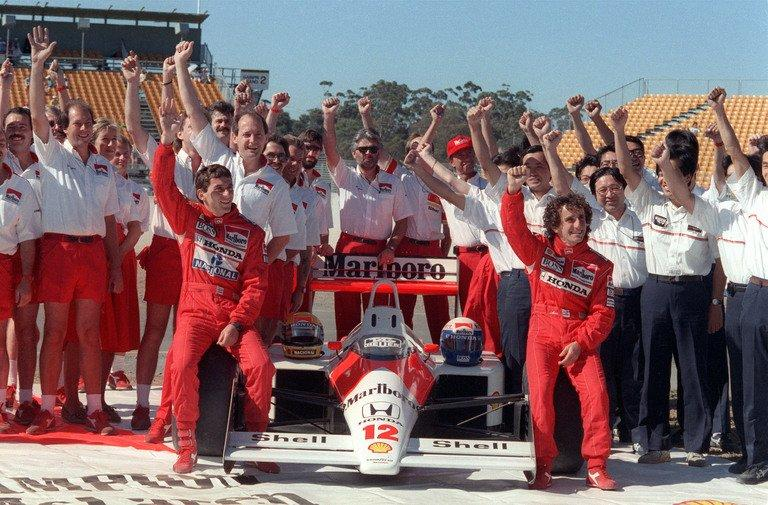Brazilian Ayrton Senna (L) raises his fist along with his team-mate Alain Prost (R), on November 12, 1988