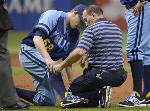 Tampa Bay Rays starting pitcher Jeremy Hellickson, left, is tended to by a trainer after taking a line drive to the leg from Detroit Tigers' Prince Fielder during the third inning of a baseball game in St Petersburg, Fla., Saturday, June 30, 2012. Hellickson left the game due to the injury. (AP Photo/Phelan M. Ebenhack)