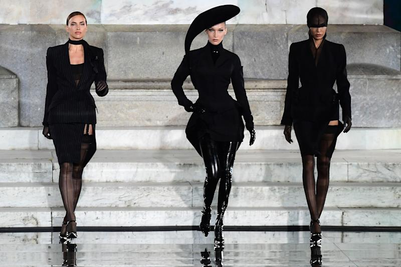 Russian model Irina Shayk (L) and US model Bella Hadid (C) present a creation during the presentation of French fashion editor Carine Roitfeld's CR Runway concept with Italian luxury retailer LuisaViaRoma, on the Piazzale Michelangelo esplanade on June 13, 2019 within the Pitti Immagine Uomo fashion fair in Florence. - The show features some 90 fall 2019 mens and womens looks curated by French fashion editor Carine Roitfeld, which will then begin retailing on LuisaViaRomas international website, rolling out in various drops throughout the year. (Photo by Miguel MEDINA / AFP)MIGUEL MEDINA/AFP/Getty Images ORIG FILE ID: AFP_1HH8VU