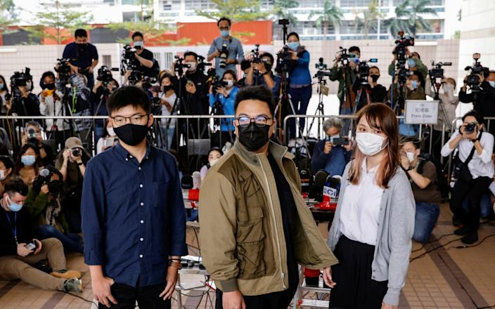 Pro-democracy activists Ivan Lam, Joshua Wong and Agnes Chow arrive at the West Kowloon Magistrates' Courts - Reuters