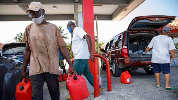 PHOTO: A resident carries full gas containers at Cooper's gas station before the arrival of Hurricane Isaias in Freeport, Grand Bahama, Bahamas, July 31, 2020. (Tim Aylen/AP)