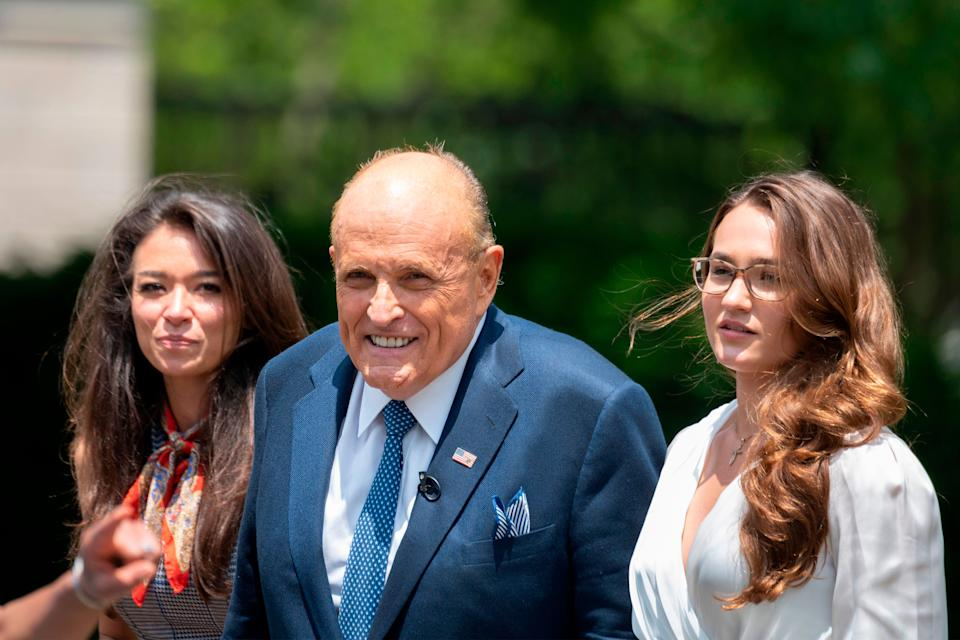 Rudy Giuliani, President Donald Trump's personal attorney, walks with his aide Christianne Allen (right) and One America News Network's Chanel Rion on July 1 after speaking at the White House. (Photo: JIM WATSON via Getty Images)
