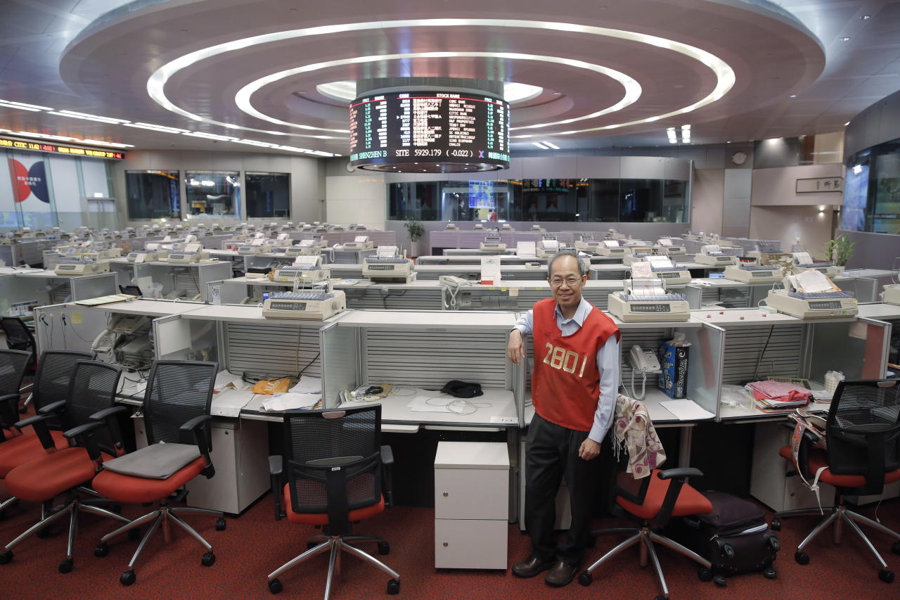 In this Oct. 19, 2017 photo, Yip Wing-keung, a trading manager at local brokerage Christfund Securities, wearing his red trading jacket, poses for a photo at the Hong Kong Stock Exchange. Hong Kong's last remaining stock market floor traders are taking their final orders as the exchange prepares to shut its trading hall, joining other world exchanges in going fully automated. (AP Photo/Kin Cheung)