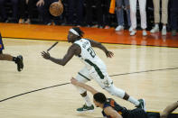 Milwaukee Bucks guard Jrue Holiday (21) looks toward the ball over Phoenix Suns guard Devin Booker during the second half of Game 5 of basketball's NBA Finals, Saturday, July 17, 2021, in Phoenix. (AP Photo/Ross D. Franklin)