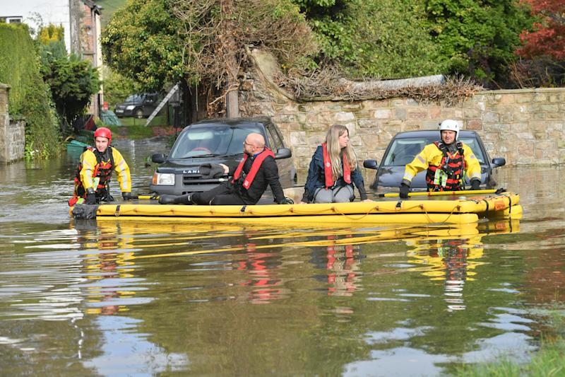 Members of Gloucestershire Fire & Rescue Service rescue brother and sister, Jennie and Eddie Allen, who were on holiday and left stranded in a holiday property surrounded by flood water from the River Wye in Lower Lydbrook, Gloucestershire.