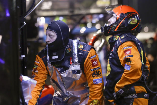 Crew members for Martin Truex Jr. watch from the pits during the NASCAR Cup Series auto race Wednesday, May 20, 2020, in Darlington, S.C. (AP Photo/Brynn Anderson)