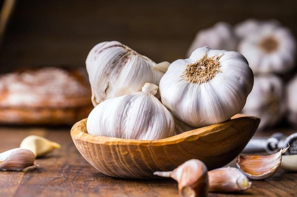 """<span>Mouth pain is pretty awful and many people will try anything for relief, including home remedies. </span><span>You may have heard that garlic is a cure for a toothache, which turns out to be true.</span> <span>""""When you crush garlic cloves, they release allicin,"""" says <strong><a href=""""https://www.drstevenlin.com/dr-steven-lin/"""" rel=""""nofollow noopener"""" target=""""_blank"""" data-ylk=""""slk:Steven Lin"""" class=""""link rapid-noclick-resp"""">Steven Lin</a></strong>, DDS, author of <a href=""""https://fave.co/2TsSv56"""" rel=""""nofollow noopener"""" target=""""_blank"""" data-ylk=""""slk:The Dental Diet"""" class=""""link rapid-noclick-resp""""><em>The Dental Diet</em></a>. """"This is a natural antibacterial agent, and it can help you with your tooth pain. Consider chewing on a piece of raw garlic, or rinsing with garlic water."""" That said, if your tooth pain persists, <a href=""""https://bestlifeonline.com/going-to-the-dentist-coronavirus/?utm_source=yahoo-news&utm_medium=feed&utm_campaign=yahoo-feed"""" rel=""""nofollow noopener"""" target=""""_blank"""" data-ylk=""""slk:get it checked by your dentist"""" class=""""link rapid-noclick-resp"""">get it checked by your dentist</a>.</span>"""