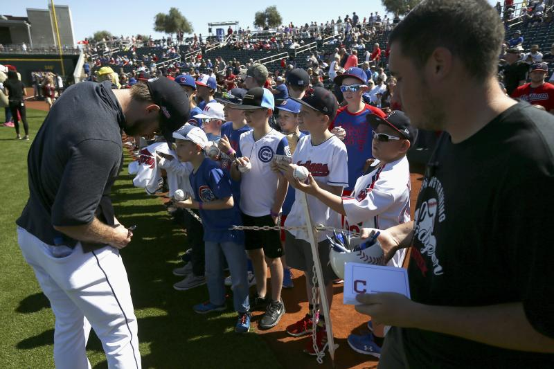 Cleveland Indians' Mike Freeman, left, signs autographs for fans as a Goodyear Stadium employee holds a container of pens and autograph cards prior to the team's spring training baseball game against the Chicago Cubs on Saturday, March 7, 2020, in Goodyear, Ariz. The stadium offered the items for players to sign autographs as a precaution for the coronavirus. (AP Photo/Ross D. Franklin)