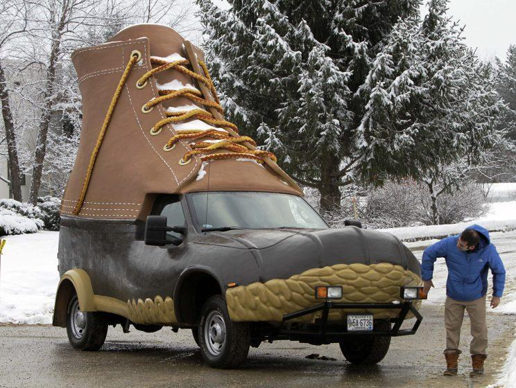 A man wipes off the headlights of the L.L. Bean Bootmobile in the parking lot at the facility where the famous outdoor boot is made. (AP Photo/Pat Wellenbach)