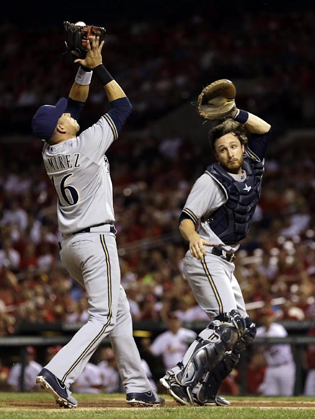 Milwaukee Brewers third baseman Aramis Ramirez, left, catches a pop up by St. Louis Cardinals' Matt Holliday for the out as Brewers catcher Jonathan Lucroy moves out of the way during the first inning of a baseball game, Thursday, Sept. 12, 2013, in St. Louis. (AP Photo/Jeff Roberson)