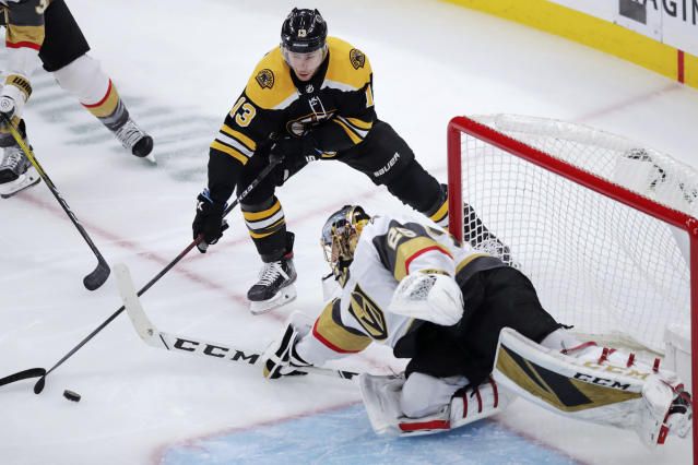 Vegas Golden Knights goaltender Marc-Andre Fleury, right, reaches for the puck against Boston Bruins center Charlie Coyle (13) during the first period of an NHL hockey game in Boston, Tuesday, Jan. 21, 2020. (AP Photo/Charles Krupa)