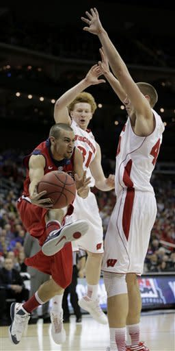 Mississippi guard Marshall Henderson, left, passes around Wisconsin forward/center Jared Berggren, right, and forward Mike Bruesewitz (31) during the second half of a second-round game of the NCAA college basketball tournament Friday, March 22, 2013, in Kansas City, Mo. (AP Photo/Charlie Riedel)