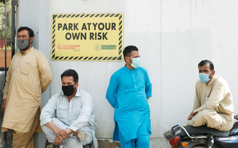 FILE PHOTO: Men wearing face masks wait to see their relatives who were admitted after being affected from a suspected gas leak, at the hospital entrance in Karachi