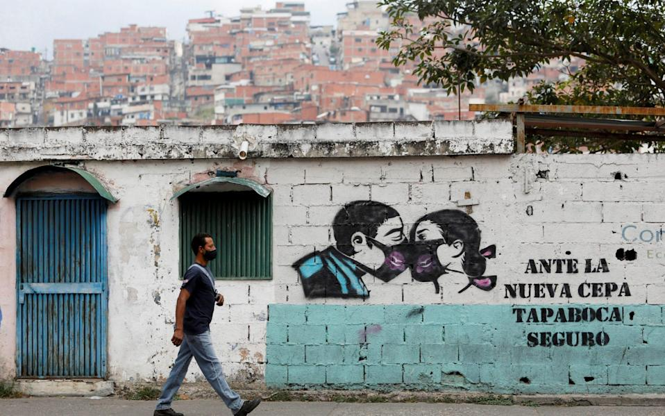 """Graffiti reads """"In the face of the new strain, face mask for sure"""" amid a spike in infections in Caracas - Reuters"""