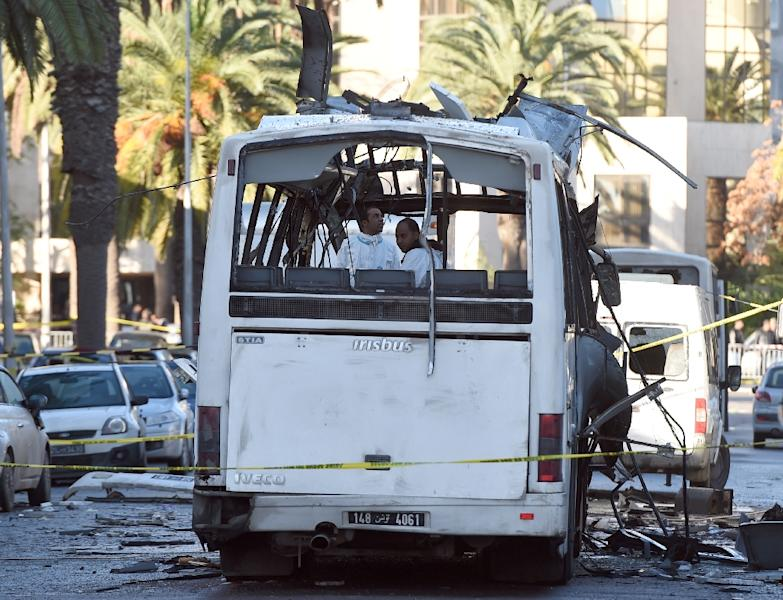Tunisian forensic police inspect the wreckage of a bus in the aftermath of a bomb attack on the vehicle transporting Tunisia's presidential guard in central Tunis on November 25, 2015 (AFP Photo/Fethi Belaid)