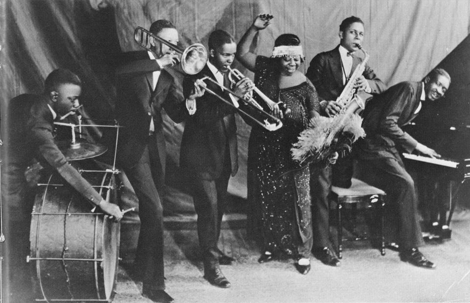 "CHICAGO - CIRCA 1924:  ""Mother of the Blues"" Ma Rainey and her band the Rabbit Foot Minstrels with Ed Pollock, Albert Wynn, Thomas A. Dorsey (on piano at right) Ma (Gertrude) Rainey, Dave Nelson and Gabriel Washington pose for a portrait circa 1924 in Chicago, Illinois.  (Photo by Michael Ochs Archives/Getty Images)"