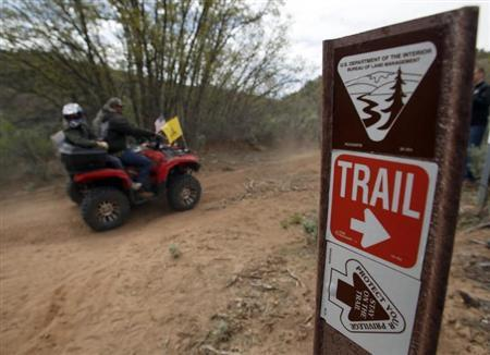 ATV riders ride past a trail sign in Recapture Canyon outside Blanding
