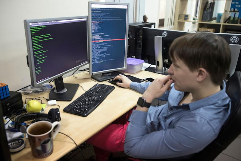 An employee of Global Cyber Security Company Group-IB develops a computer code in an office in Moscow, Russia, Wednesday, Oct. 25, 2017. A new strain of malicious software has paralyzed computers at a Ukrainian airport, the Ukrainian capital's subway and at some independent Russian media. Moscow-based Global Cyber Security Company Group-IB said in a statement Wednesday the ransomware called BadRabbit also tried to penetrate the computers of major Russian banks but failed. None of the banks has reported any attacks. (AP Photo/Pavel Golovkin)