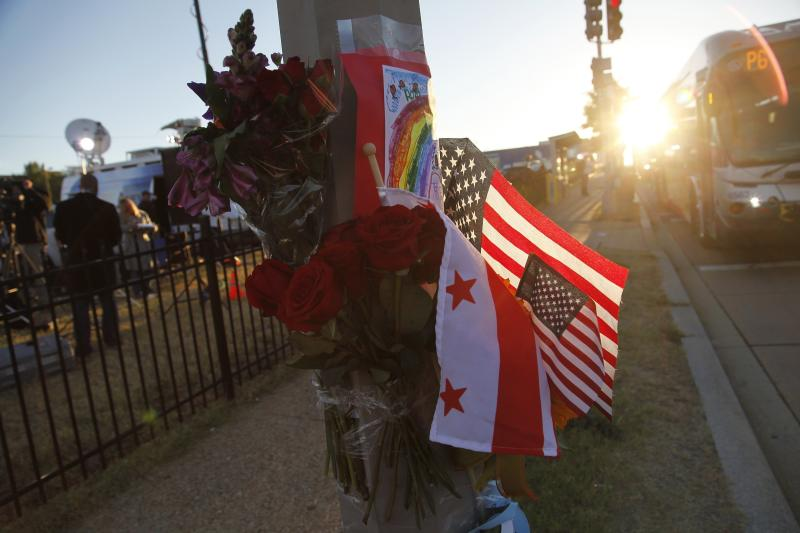 Flowers, flags and a child's drawing are pictured at a makeshift memorial outside the Navy Yard after a gunman killed 12 people, in Washington