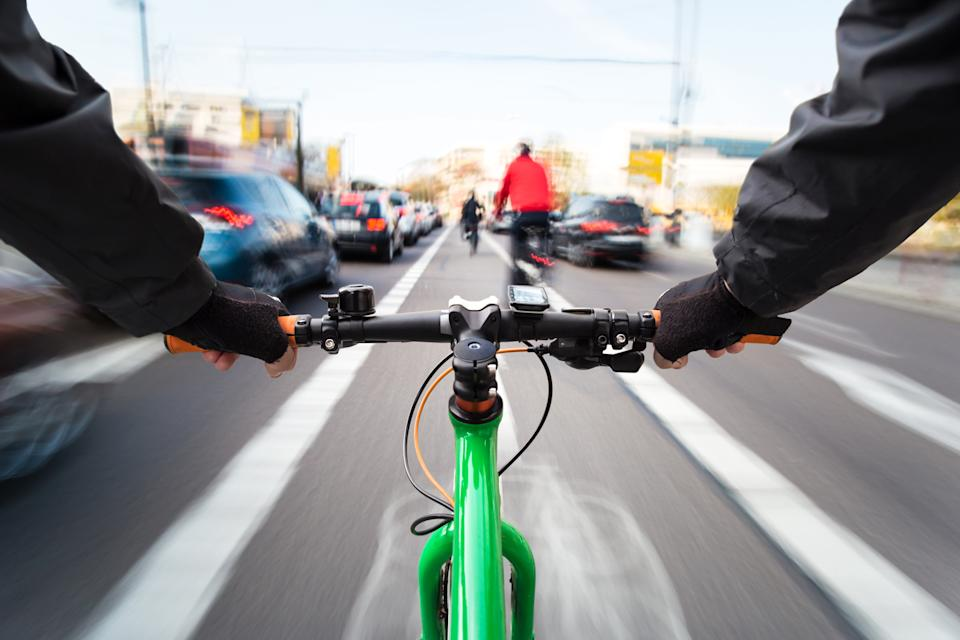 Cyclist drives past cars. Source: Getty Images