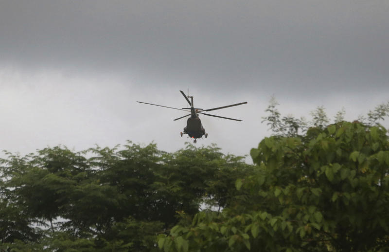 A helicopter believed to be carrying one of the rescued boys from the flooded cave lands in Chiang Rai as divers evacuated the remaining boys and their coach trapped at Tham Luang cave in the Mae Sai district of Chiang Rai province, northern Thailand, Tuesday, July 10, 2018. Thai Navy SEALs say all 12 boys and their coach were rescued from the cave, ending an ordeal that lasted more than 2 weeks. (AP Photo/Vincent Thian)
