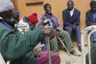 Elderly men wait to be served a meal at Melfort Old People's home on the outskirts of Harare, Zimbabwe, Sunday, July 25, 2021. The economic ravages of COVID-19 are forcing some families in Zimbabwe to abandon the age old tradition of taking care of the elderly. Zimbabwe's care homes have experienced a 60% increase in admissions since the outbreak of the pandemic in March last year. (AP Photo/Tsvangirayi Mukwazhi)