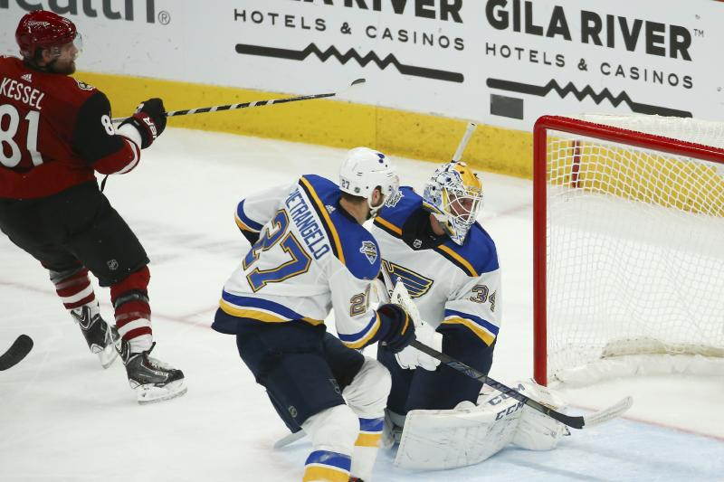 Arizona Coyotes right wing Phil Kessel (81) gets the puck past St. Louis Blues goaltender Jake Allen (34) and Blues defenseman Alex Pietrangelo (27) for a goal during the third period of an NHL hockey game Tuesday, Dec. 31, 2019, in Glendale, Ariz. The Coyotes defeated the Blues 3-1. (AP Photo/Ross D. Franklin)
