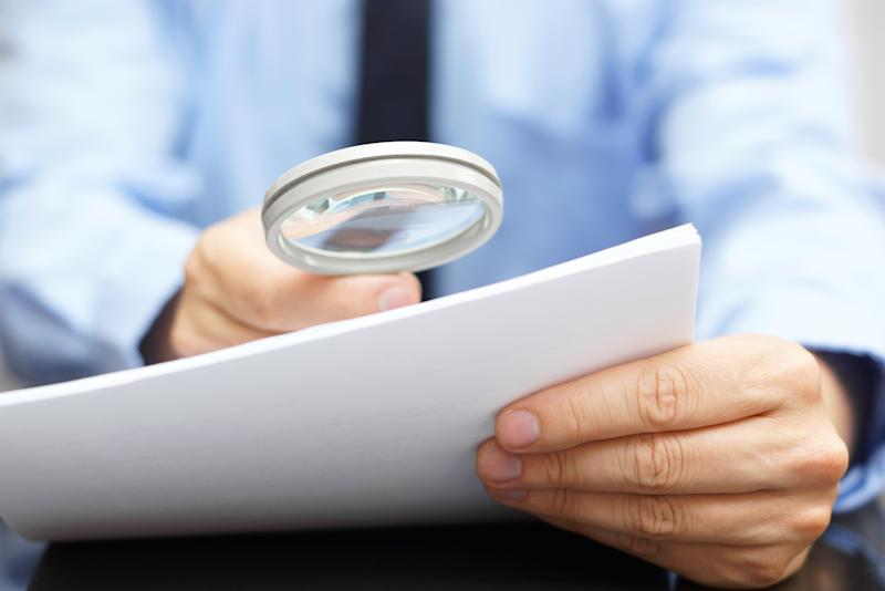 Businessman looking through contract with a magnifying glass