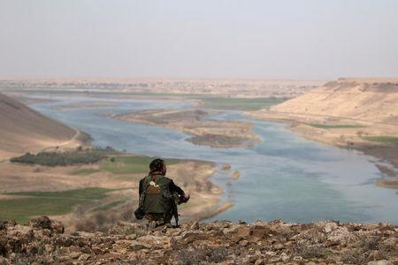 A Syrian Democratic Forces(SDF) fighter rests while looking over the Euphrates River, north of Raqqa city, Syria March 8, 2017. REUTERS/Rodi Said