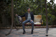 Palestinian Karam Qawasmi, who was shot in the back by Israeli forces in an incident caught on video last year, sits in his garden, in the West Bank city of Hebron, Sunday, Nov. 10, 2019. In his first interview since the video emerged last week, Karam Qawasmi said he was run over by a military jeep, then beaten for several hours before troops released him, only to shoot him in the back with a painful sponge-tipped bullet as he walked away. (AP Photo/Majdi Mohammed)