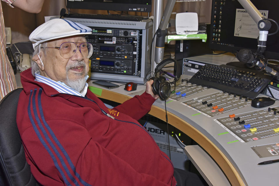 """In this photo provided by Radio Television Hong Kong (RTHK), Ray Cordeiro, also known as Uncle Ray, gestures after he finished his last show """"All The Way with Ray"""" at the studio in RTHK, the broadcaster in Hong Kong on Feb.15, 2021. After more than seven decades in radio, the 96-year-old Hong Kong DJ bid farewell to his listeners Saturday, May 15, 2021 with """"Time to Say Goodbye,"""" sung by Sarah Brightman and Andrea Bocelli. (Radio Television Hong Kong via AP)"""