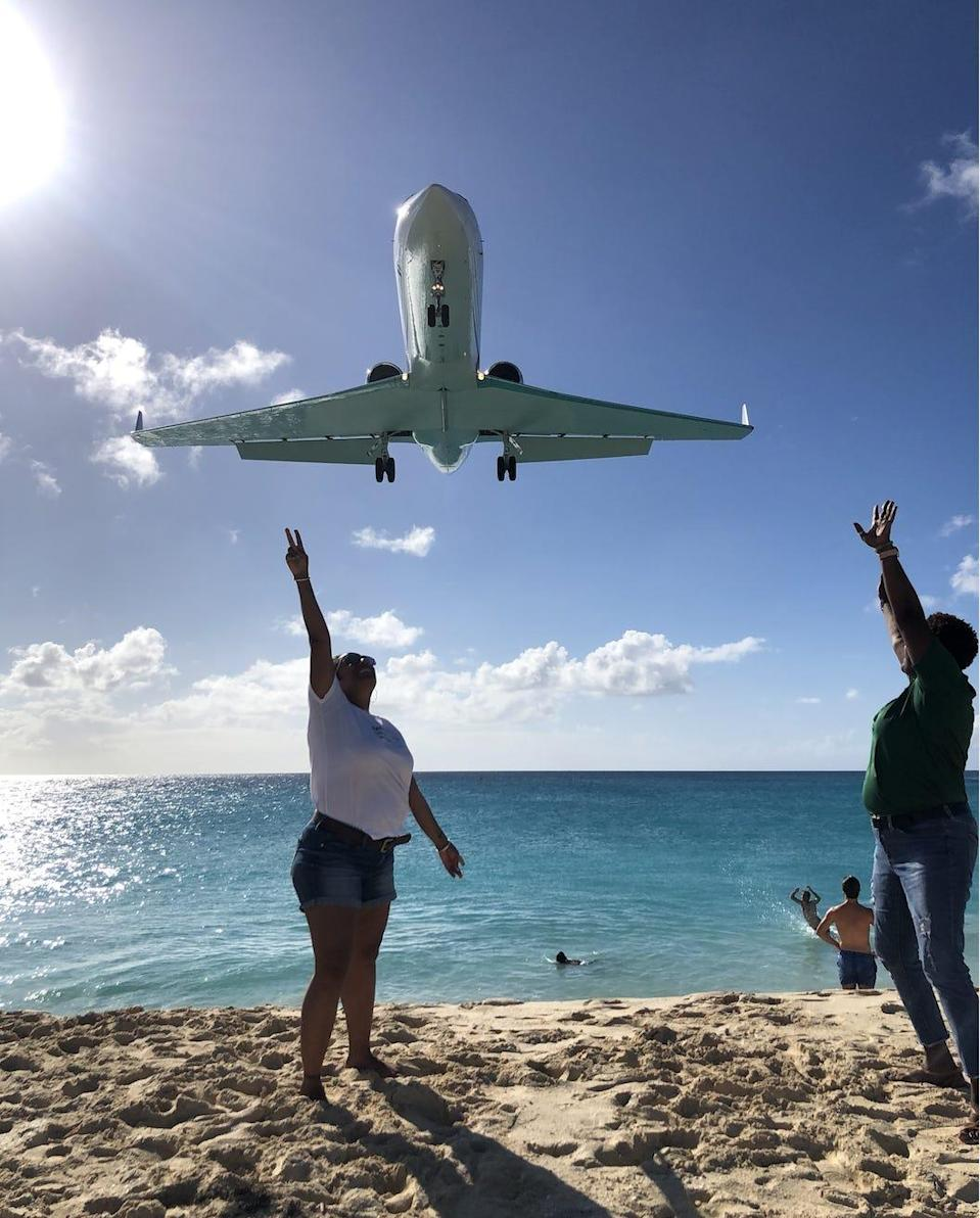 Onlookers reach up toward airplanes flying low over Maho Beach in St. Martin.