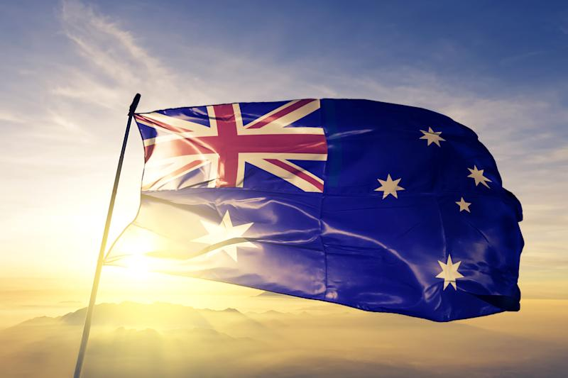 Australia Australian flag textile cloth fabric waving on the top sunrise mist fog