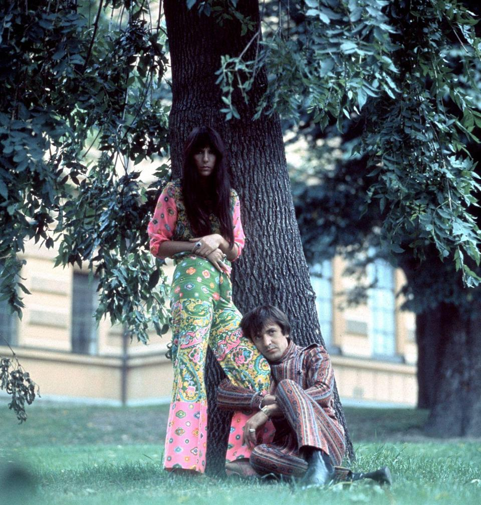 <p>Sonny and Cher posing outside in paisley and striped boho suits. </p>